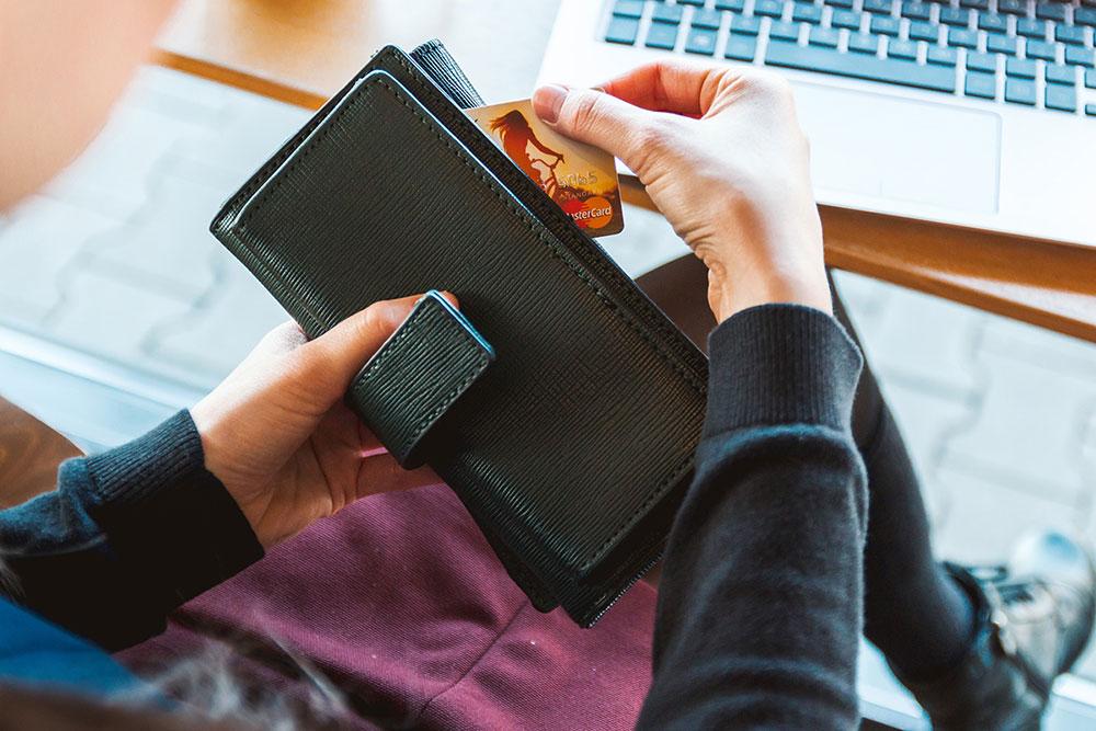 Een dame neemt een creditcard uit haar portemonnee